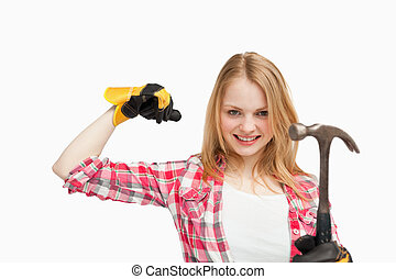 Woman smiling while holding a hammer