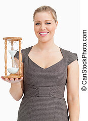 Woman smiling while holding a hourglass