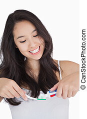 Woman smiling while holding a toothbrush and toothpaste