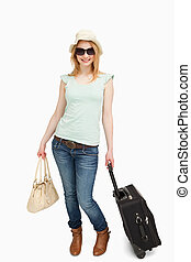 Woman smiling while holding luggages