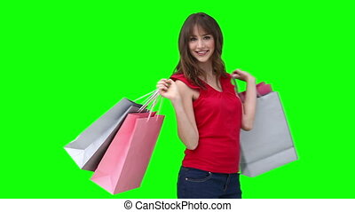 Woman smiling while holding shopping bags