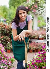Woman smiling while leaning on spade - Woman working in...
