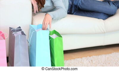 Woman smiling while looking into her shopping bags