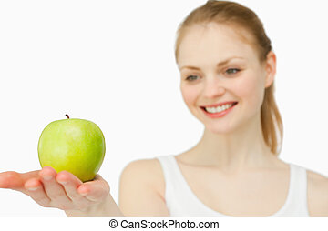 Woman smiling while presenting an apple
