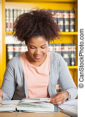 Woman Smiling While Reading Book In College Library