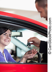 Woman smiling while receiving car keys