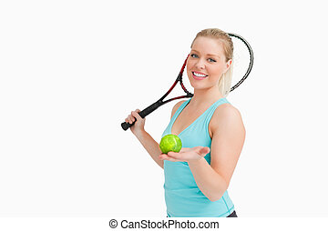 Woman smiling while showing a yellow tennis ball