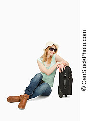 Woman smiling while sitting near a suitcase