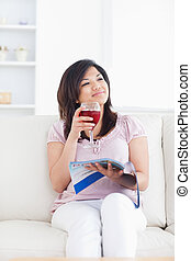 Woman smiling while sitting on a sofa and holding a glass of wine in a living room