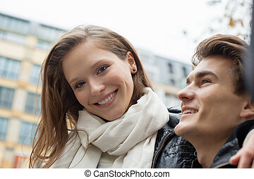 Woman Smiling While Sitting With Man Outdoors