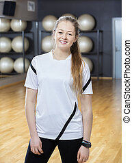 Woman Smiling While Standing In Gym