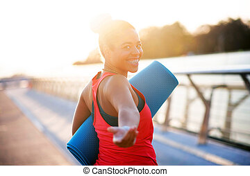 Woman smiling while walking to yoga in the morning