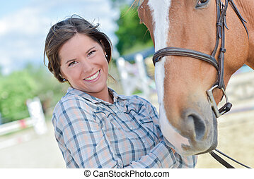 woman smiling with a horse