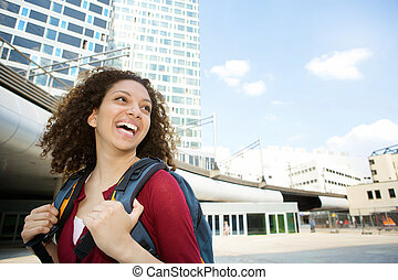 Woman smiling with backpack in the city