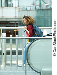 Woman smiling with bag on escalator