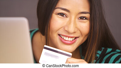 Woman smiling with credit card in hand