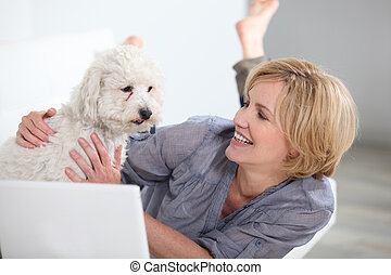 Woman smiling with dog and laptop