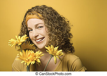 Woman smiling with flowers.