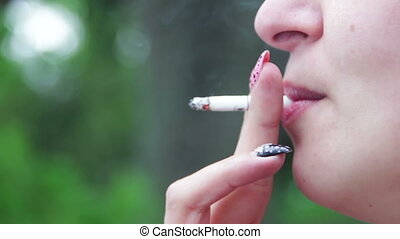 Woman Smokes a Cigarette and Blows Smoke from Her Mouth