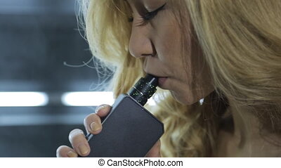 Woman smokes electronic vaporizer close up, thick stream of...