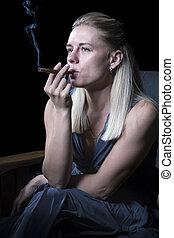 Woman smoking a cigar in an armchair