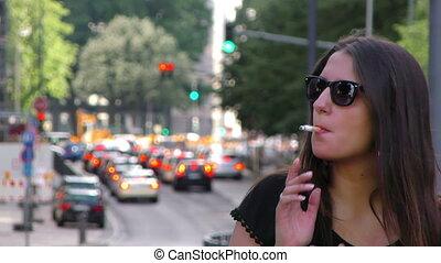 Woman Smoking and Traffic Behind