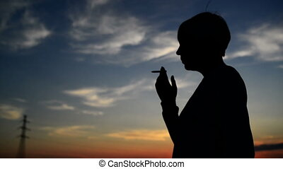 Woman smoking cigarette in sunset