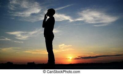 Woman smoking cigarette in sunset