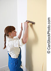 Woman smoothing down wallpaper