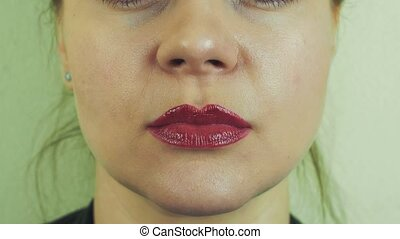 Woman smudge red pomade from lips by hand in front camera....
