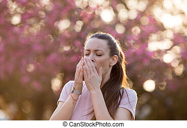 Woman sneezing because of spring pollen allergy