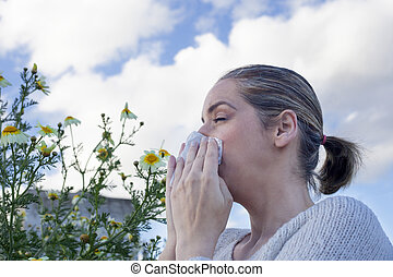 Woman sneezing in a daisy flowers meadow