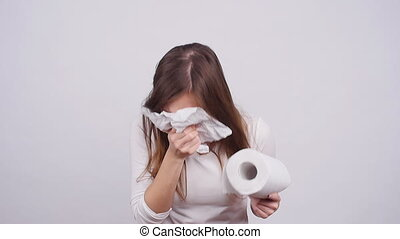 Woman sneezing in a tissue on the white background