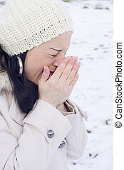woman sneezing in the snow