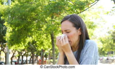 Woman sneezing outdoor in a park - Ill woman sneezing and...