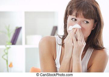 woman sneezing - sick woman on sofa with handkerchief...