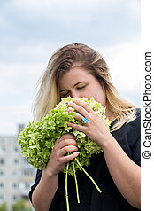 woman sniffing a bouquet of hydrangeas