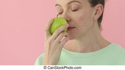 Woman sniffing an apple on light pink background - Woman...