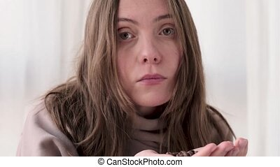 Young woman is holding coffee beans and sniffing