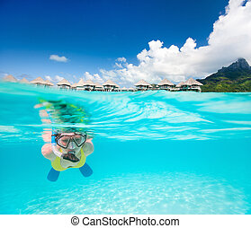 Woman snorkeling in a tropical lagoon - Woman snorkeling in...