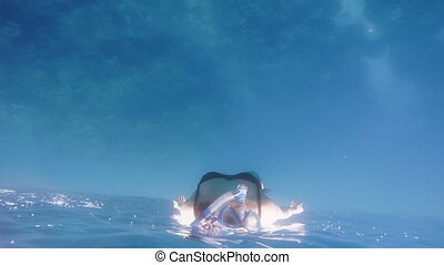 Woman snorkelling. Slow motion shot captured at an unusual...