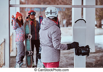 Woman snowboarder holding a board turned to greet the friends in the winter ski resort