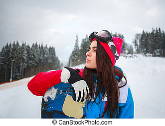 Woman snowboarder in winter at ski resort on background of pine trees
