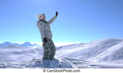 Woman snowboarder makes selfie at the top of the mountain,...