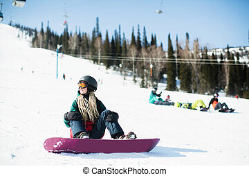 Woman snowboarder sitting on a snowy slope.