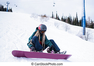 Woman snowboarder zipping up his boots while sitting on a snowy slope.