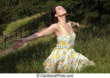 Woman soaking up summer sun in countryside - Beautiful young...