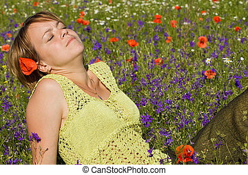 Woman soaking up the sun sitting on the flowers field