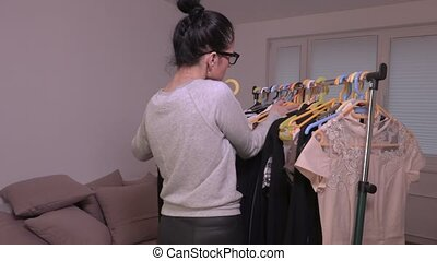 Woman sorting clothes on the rack