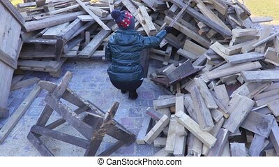 Woman sorting firewood between two piles of firewood